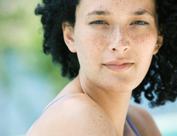 Photo d'une femme qui est à l'extérieur et plisse des yeux pour se protéger du soleil